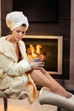 Attractive woman in front of fireplace