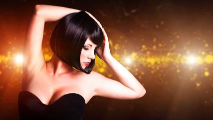attraktive schwarzhaarige Frau vor Lichterhintergrund
