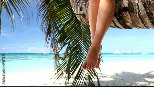 Woman sitting on palm on tropical beach, moving legs
