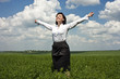 portrait of happy businesswoman in green field
