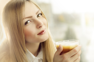 Beautiful blond girl holding glass with cappuccino