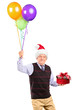 Joyful mature gentleman with christmas hat holding gift and bunc