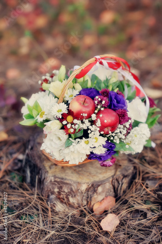 on an old stump basket with flowers and red apples