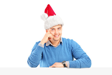 Smiling male wearing a santa hat and posing behind a panel