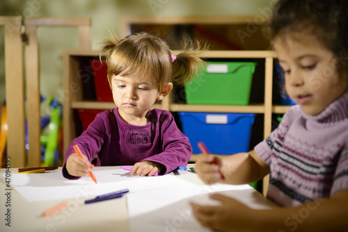 Children and fun, two preschoolers drawing in kindergarten