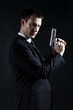 Secret agent holding handgun against black background