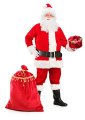Santa Claus holding a gift and bag full of presents next to him