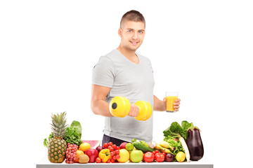 Guy holding a dumbell and glass of juice behind a pile of fruits