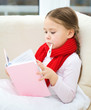 Ill little girl with thermometer is reading book
