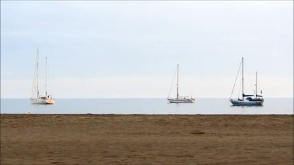 Drei Segelboot liegen vor dem Strand