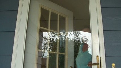 Old Woman Answering Front Door Waving In