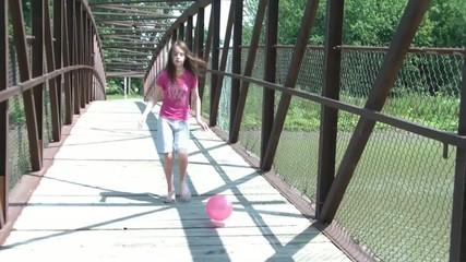 Girl Kicks Ball Over Bridge