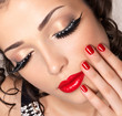 Model with red nails, lips and creative eye makeup