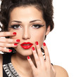 Beautiful fashion model with red manicure and lips