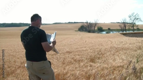 Man Reading Newspaper in Wheat Field