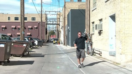 Man Holding Stereo on Shoulder Spins in Alley