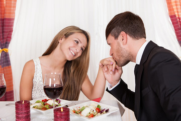 Man kissing a woman's hand at a romantic dinner