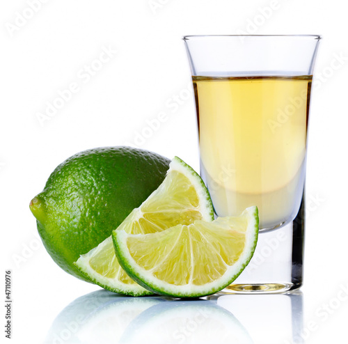 Gold tequila shot with lime isolated on white