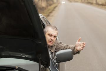 Man sitting in broken car  on the road