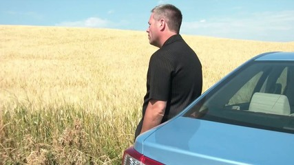 Man in Wheat Field Leaning Against Car