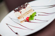 Tiramisu cake with a cherry and mint on white plate on table in