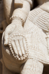 Carving of a woman's hand holding rosary beads