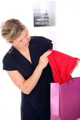 Beautiful mid age blonde woman checking shopping bags