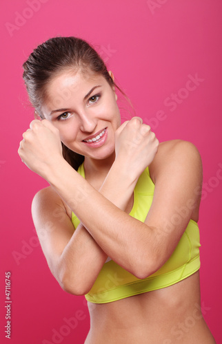 Beautiful slim sporty girl portrait over a pink