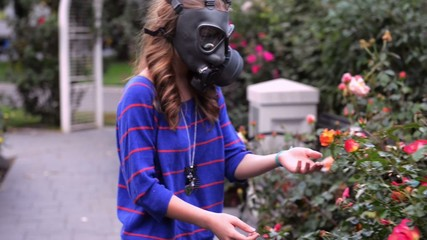 girl in gas masks smells flowers