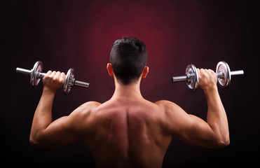 Muscular young man lifting weights from back against black backg