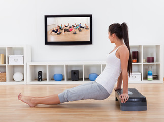 Athletic woman doing exercises in her livingroom