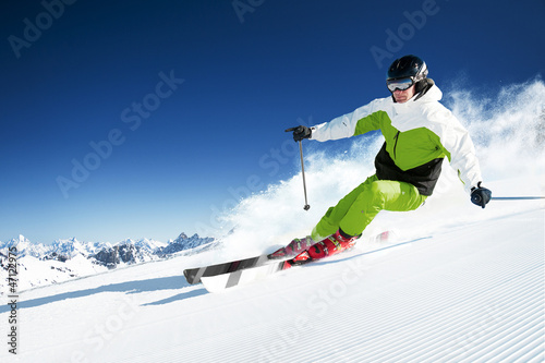 Skier in mountains, prepared piste and sunny day - 47122975