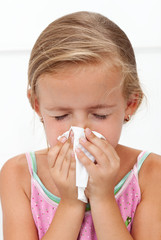 Little girl with the flu blowing nose