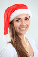 Picture of pretty christmas girl in santa hat, smiling isolated