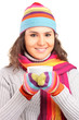 A smiling female wearing a hat and scarf and holding a cup of te