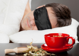 Man with Sleeping mask sleep on a bed, cup of herbal tea in the