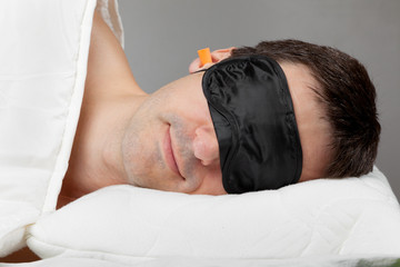 Man with Sleeping mask sleep and earplugs lying in bed
