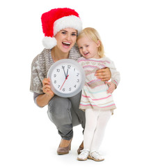 Happy mother in Christmas hat and baby girl holding clock