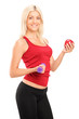 Attractive athlete female holding a dumbbell and apple