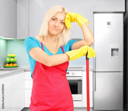 Tired female cleaner resting after cleaning a kitchen