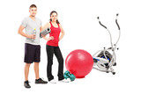 Male and female athlete posing next to an excerise equipment