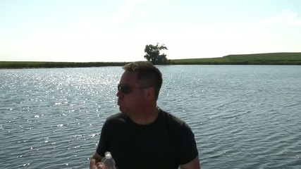Man Drinks Water Bottle with Lake Background