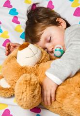 Sweet child sleeping with teddy bear