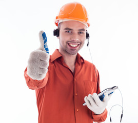 A builder with telephone and giving a thumbs up.