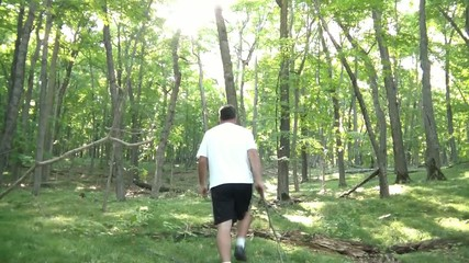 Man Hiking in Forest with Stick