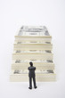 Businessman figurine standing in front of stack of dollars