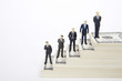 Businessman figurines standing on dollars stairway