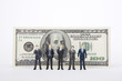Businessman figurines standing in front of 100 dollar note
