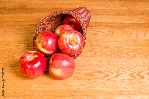Red apples on table in cornucopia