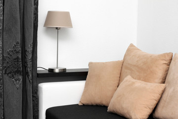 couch with pillows and lamp on the shelf